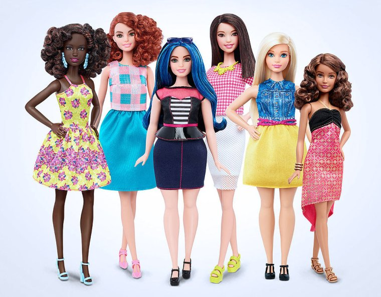 Six Barbie dolls with diverse bodies and skin tones. From left to right, a petite dark-skinned doll, a tall red-haired doll, a curvy doll with blue hair, a tall Asian doll, a curvy blonde doll, and a petite brunette doll.
