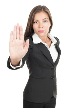 "Woman in business dress holds up her hand in the ""stop"" motion"