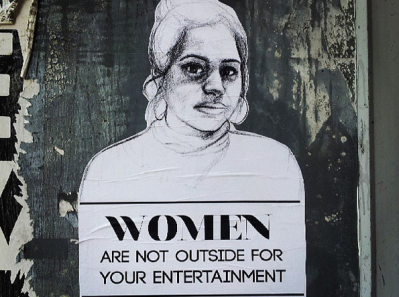 "An image of street art with a drawn woman, and text below reading ""women are not outside for your entertainment""."