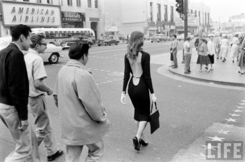 A black and white image of a woman being followed by three men on the street.