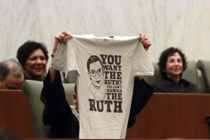 "Ruth Bader Ginsburg holds up a t-shirt with her face and the words, ""You want the Ruth? You can't handle the Ruth."""