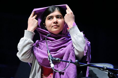 Malala Yousafzai stands behind a microphone, wrapped in a purple headscarf.