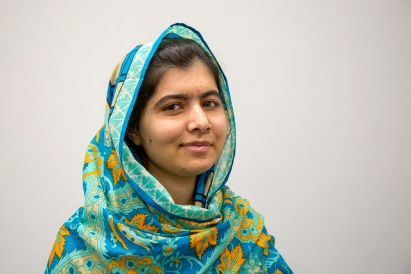 Malala Yousafzai smiles at the camera, wrapped in a bright blue and yellow headscarf.