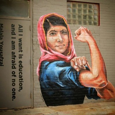 "Street art depicts Malala Yousafzai as ""Rosie the Riverter""."