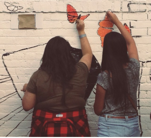 The author (on the left) painting a butterfly mural