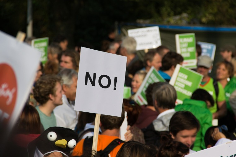 """Protesters holding signs and a sign that says """"No""""."""