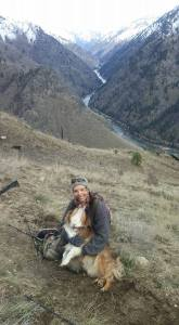 Author and her dog sitting on a slope above the Salmon River