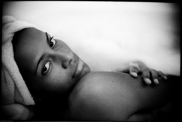 African american woman staring into a camera sitting in a bathtub