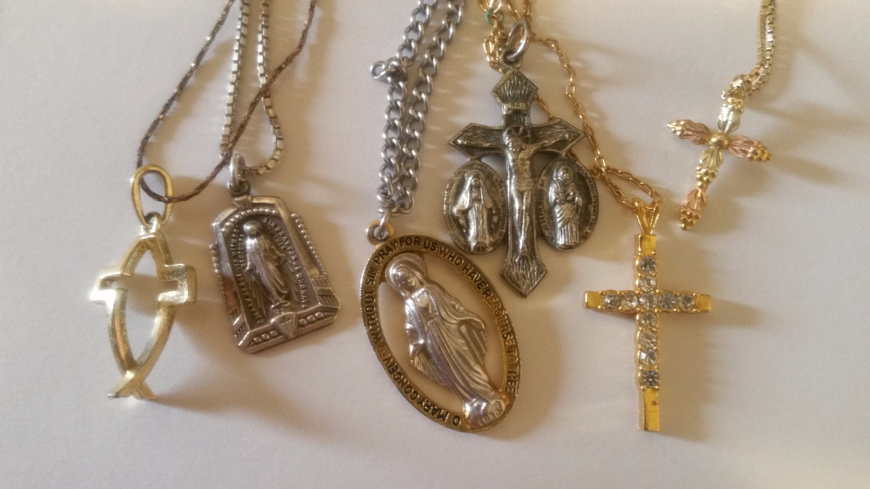 Religious themed necklaces sitting on a white background.