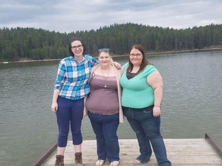 Three friends standing on a dock looking at the camera. There is a lake behind them.