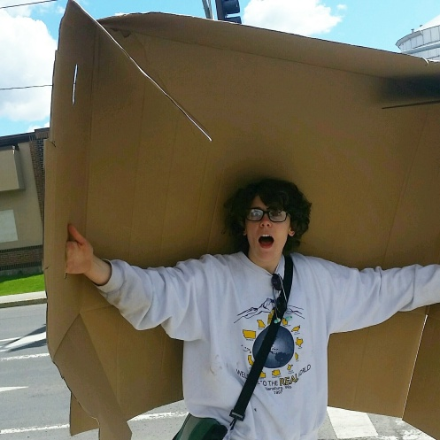 A woman with a big piece of cardboard.