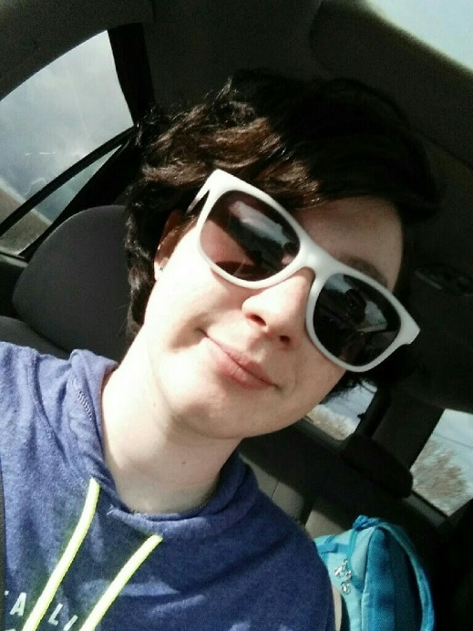 the author wearing white sunglasses with the sun on her face while riding in a car