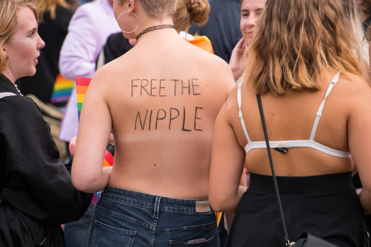 "Pictured are the backs of two womxn, one without a bra and one with. The womxn not wearing the bra has ""Free the Nipple"" written across their back."