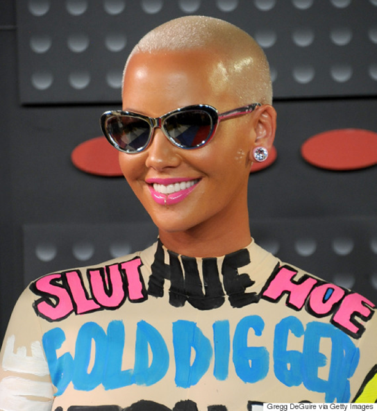 "Photo of Amber Rose, smiling with buzz cut blonde hair wearing an outfit that says, ""slut, hoe, gold digger."""