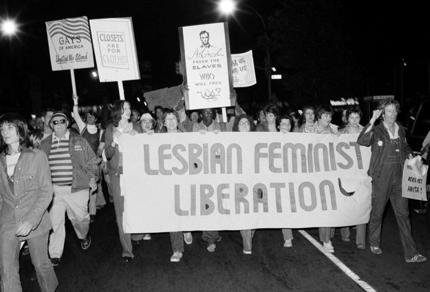 "A black and white photo from the 1960s depicting a lesbian feminist march. Walkers are holding signs that say ""Lesbian Feminist Liberation"" and ""Gays of America United We Stand."""