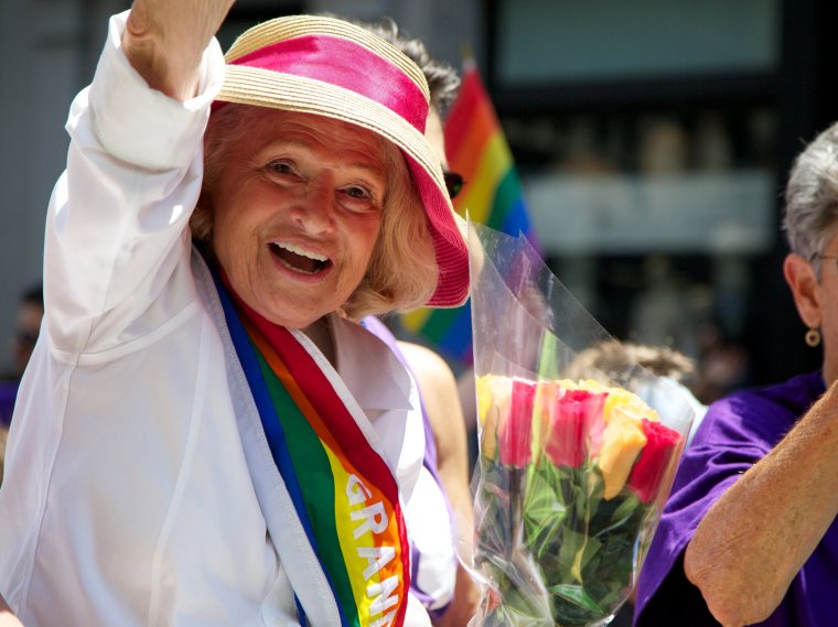 Edith Windsor, later in her life, waving to onlookers as Grand Marshall of a Pride Parade.