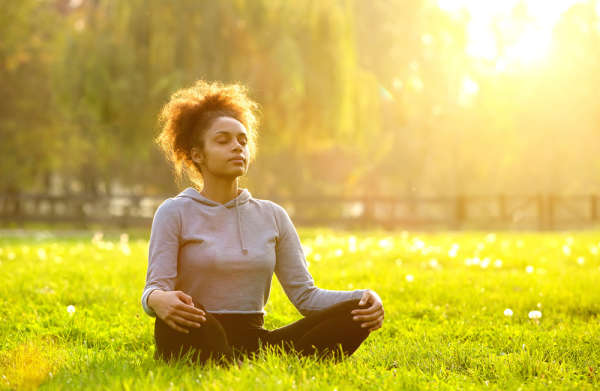 Womxn in a ponytail meditating in a field with the sun shinning behind her.