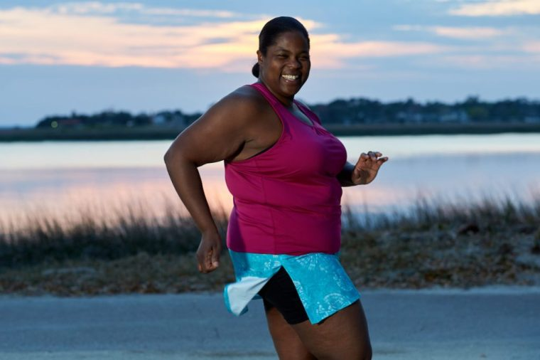 Mirna, an African American woman, smiles at the camera as she runs. She wears a bright pink tank top and a blue running skirt.
