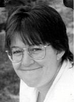 A black and white photo of a woman smiling at the camera, she has short hair and wears glasses.