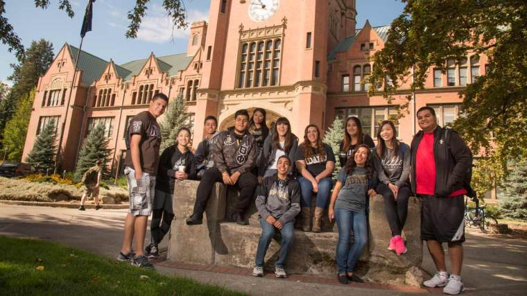 A diverse group of UI students pose in front of the Admin Building.