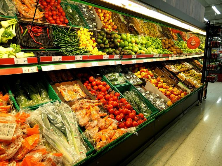 Fresh vegetables line the aisle of a grocery store.
