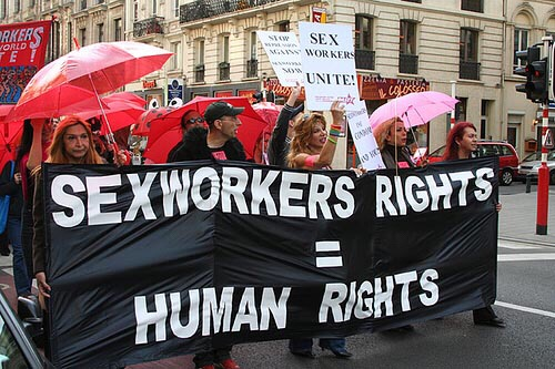 "A diverse group of protests advocating for sex workers rights. Front group holding a sign that says ""sex workers rights = human rights."""