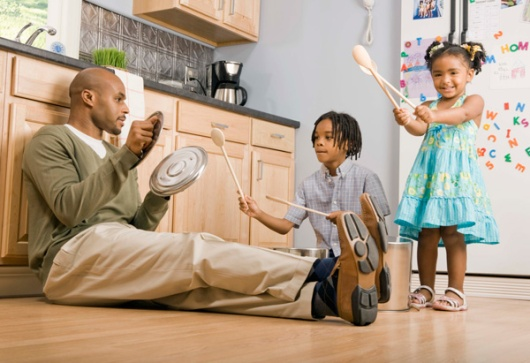 A father sits with his two kids in the kitchen playing with pots and pans
