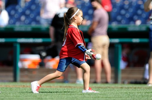 Hailey Dawson throws out the first pitch with her 3D printed hand at a baseball game in June.