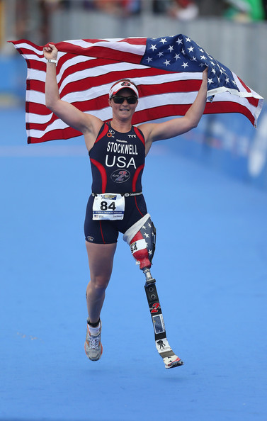 Althete Melissa Stockwell celebrates her victory holding an American flag. She has an amputated leg and competes in triathlons