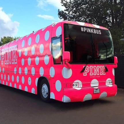 A side-angle image of a pink tour bus with white polka dots that says
