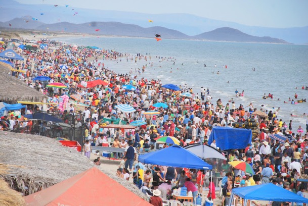 A crowded beach in Mexico where there is no visible sand there are so many people