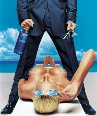 An advertisement for Skyy Vodka depicting a man standing over a woman on a beach