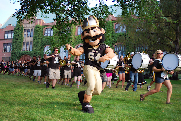 University of Idaho mascot Joe Vandal marching with the marching band behind him.
