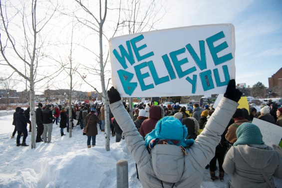 "A white sign with the text, ""we believe you"""