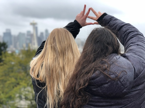 Two women give the hand gesture of their sorority Kappa Alpha Theta