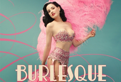 A picture of a burlesque showgirl wearing a sequenced pink and silver lingerie outfit and holding pink feathers.