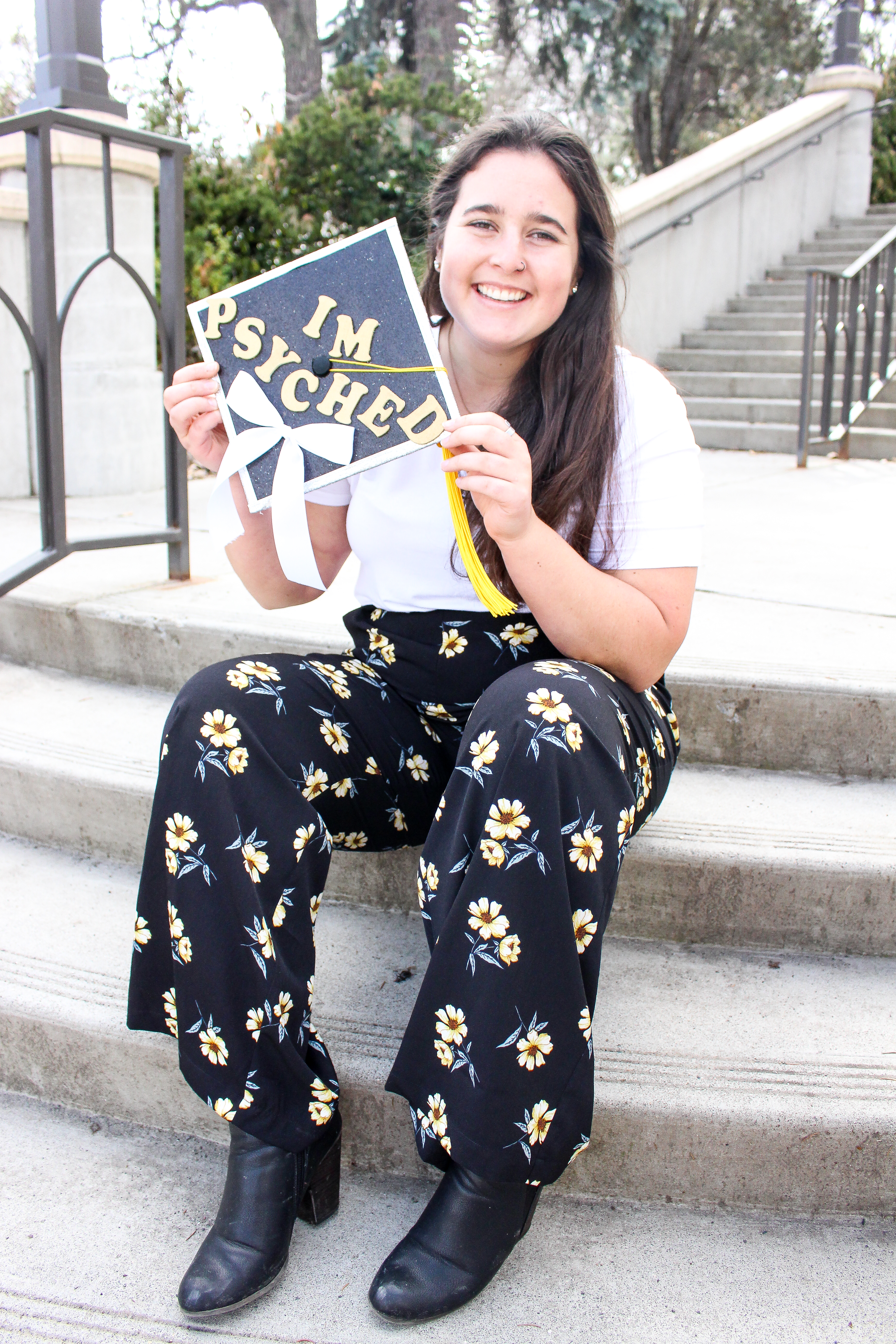 """The author holds her grad cap with the words """"I'm psyched"""" on it"""