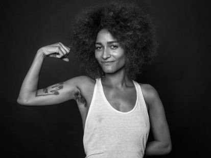 A woman with an afro flexes her bicep, showing off her armpit hair.
