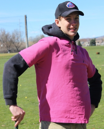 Author of article stands in pink shirt leaning on golf club at a driving range