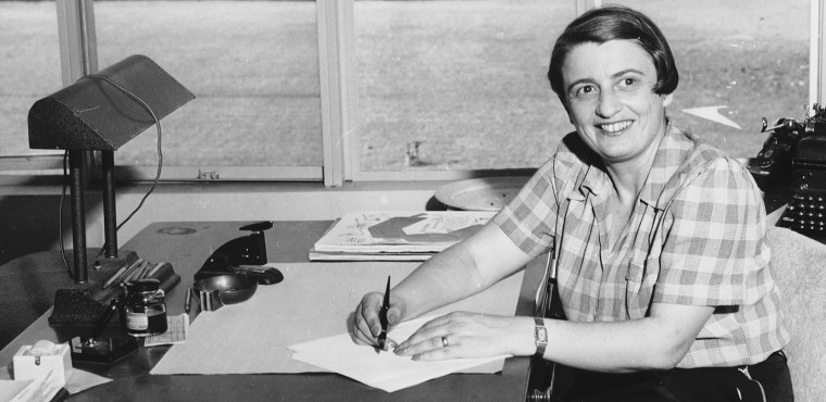 Author Ayn Rand sits at a desk smiling, in black and white