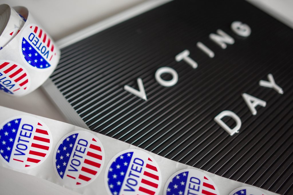 """a letter board that says """"voting day,"""" with """"I voted,"""" stickers surrounding it"""