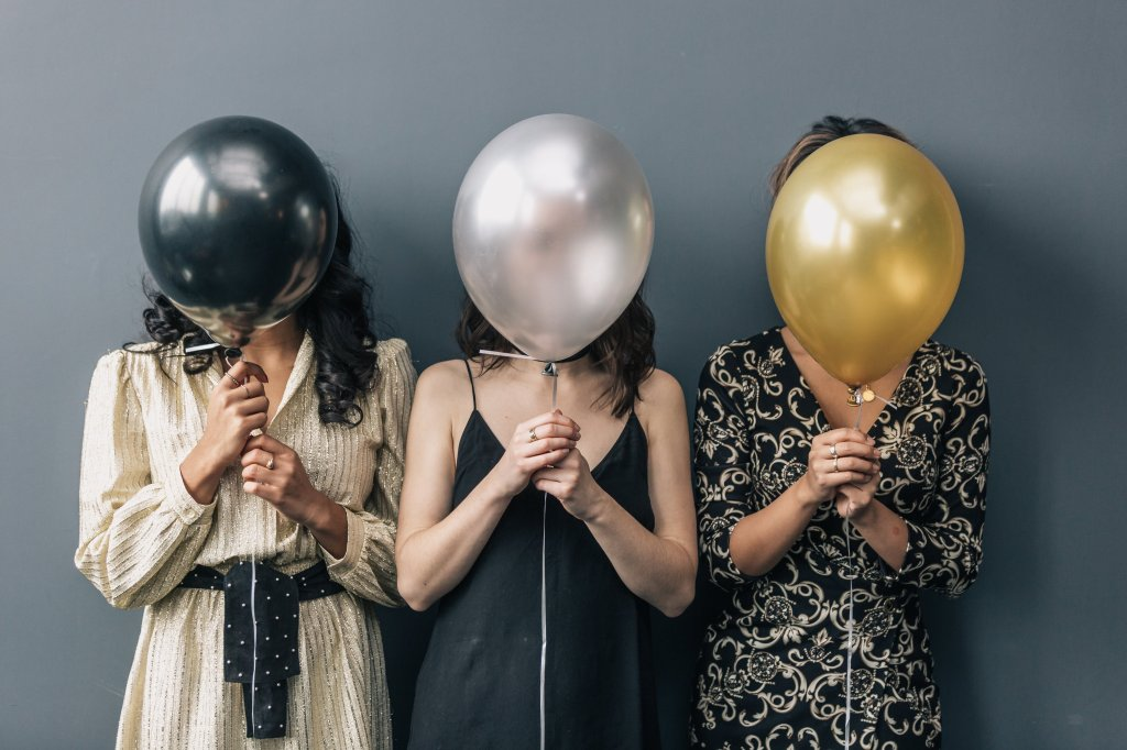 three women standing in a line holding different colored balloons over their faces