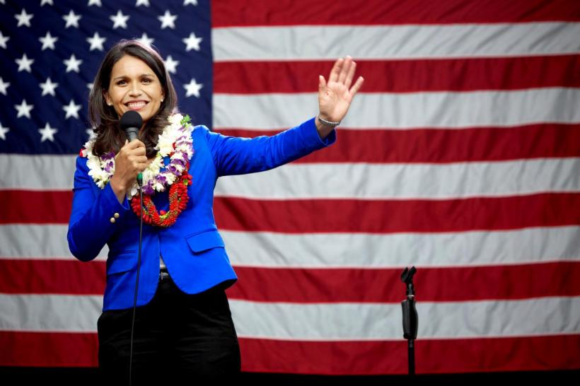 Tulsi Gabbard on Election Night, standing in front of the American flag, wearing a plethora of leis. She is waving to the crowd.
