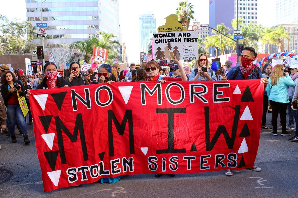 A crowd of people marching behind a large banner held by 4 people wearing masks to symbolize those who can no longer speak, that says No More Stolen Sisters on top and bottom sandwiching the letters MMIW for Women's March of 2019