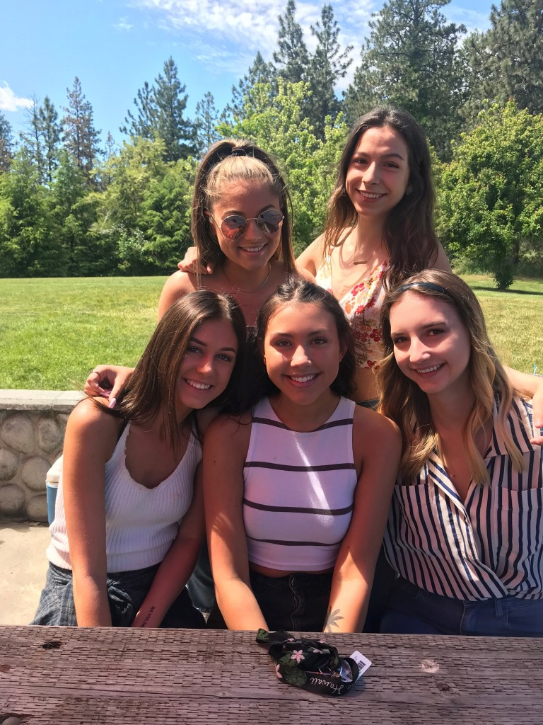 Five high school age girls sitting at a picnic table, close together, smiling.
