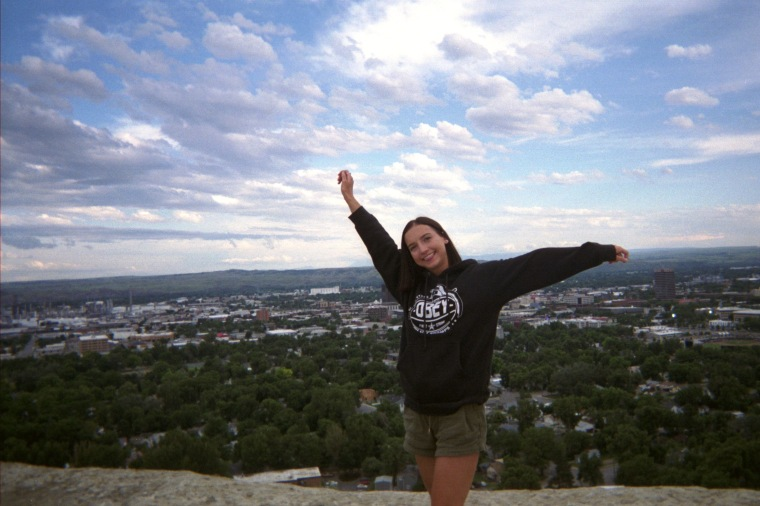 "Twenty year old white woman with short black hair, a black sweatshirt and dark green shorts posing in front of ""The Rims"", a scenic view point in Billings Montana."