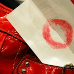 A bright red lipstick stain on the back of a receipt stuck hanging out of the pocket of a red handbag