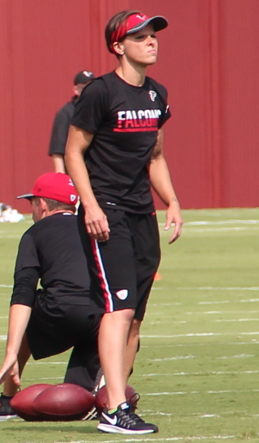 Picture of Katie Sowers. A young, fit woman with short, light brown hair. She's wearing black shorts and a black shirt sporting the Atlanta Falcons' name and a red Falcons' visor.