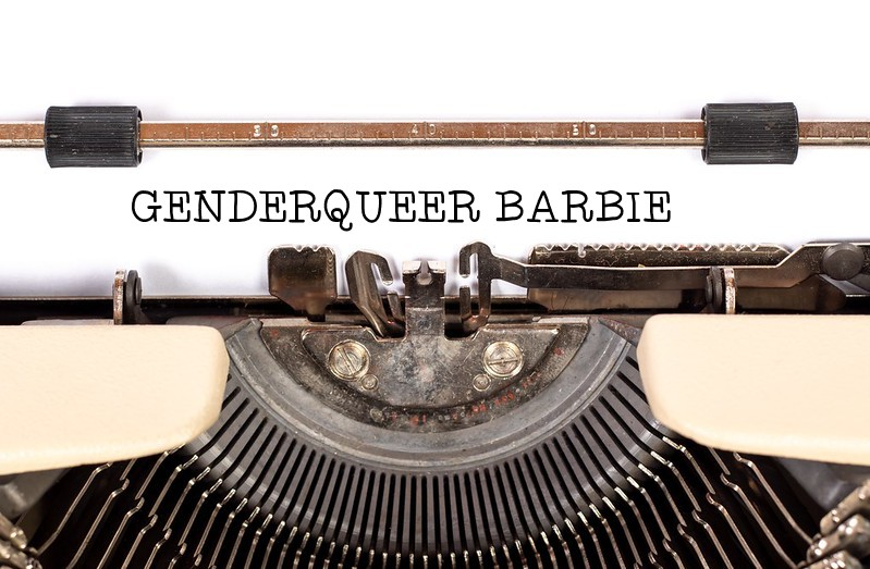 Image is of an old fashioned typewriter with the words 'GenderQueer Barbie' typed across it.
