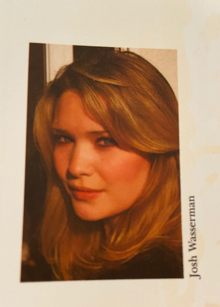 A blonde haired woman stares into the camera. It is a head shot for an author's biography.